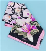 Sale 9083F - Lot 55 - A VERSACE FLORAL SILK SCARF; magnolias and tulips on a pale pink with black circles background, hand rolled hem, size 88 x 88cm.