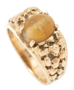 Sale 9164J - Lot 378 - A GENTS 14CT GOLD STONE SET RING; centring a 9.7 x 8mm cabochon cats eye chrysoberyl (cracked and abraded), to organic shoulders, si...