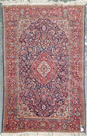 Sale 8882 - Lot 1020 - Persian Possibly Kirman Wool Carpet, with white medallion on navy blue ground, filled with arabesques (210 x 130cm)