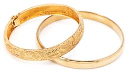 Sale 9132 - Lot 601 - TWO GOLD PLATED BANGLES; 10mm wide hinged with etched Chinese design, internal diam. 58mm, other 8mm wide, internal diam. 64mm.