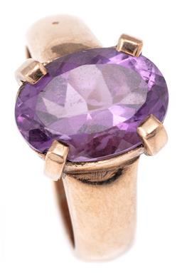 Sale 9124 - Lot 531 - A 9CT GOLD AMETHYST RING; four claw set with an oval cut amethyst of approx. 5.70ct on tapered shank, size R1/2, width 14mm, wt. 9.76g.