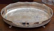 Sale 8677B - Lot 591 - A silver plated galleried tray raised on four paw feet with pierced surround, Length 58cm