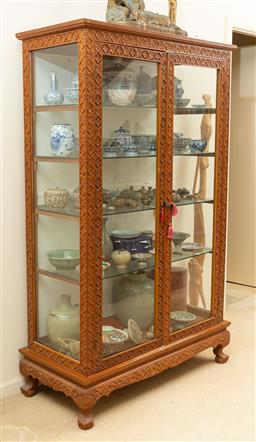 Sale 9164H - Lot 16 - A teak carved display cabinet with four glass internal shelves, raised on squat feet, Height 179cm x Width 110cm x Depth 49cm