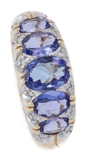 Sale 9029 - Lot 375 - A TANZANITE AND DIAMOND BRIDGE RING; set in 9ct gold with 5 graduated oval cut tanzanites adjacent to 12 round brilliant cut diamond...