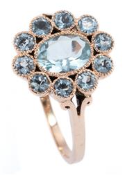 Sale 8937 - Lot 390 - AN ANTIQUE STYLE AQUAMARINE CLUSTER RING; centring an oval cut pale blue aquamarine to surround of 10 round cut blue topaz, size O,...