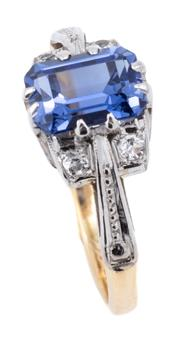 Sale 9083 - Lot 552 - A DECO STYLE STONE SET RING; set in two tone 18ct gold with a step cut synthetic blue sapphire and 4 round cut white sapphires, size...