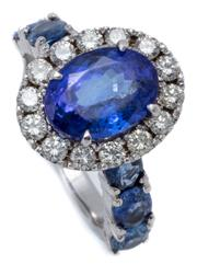 Sale 9066A - Lot 49 - A TANZANITE DIAMOND AND SAPPHIRE RING; centring an oval cut tanzanite of approx. 3.7ct encircled by 14 round brilliant cut diamonds...