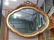 Sale 8598 - Lot 1021 - Ornate Shaped Gilt Framed Mirror, with moulded border & surmounted by leaves & flowers (72 x 84cm)