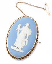 Sale 8991 - Lot 345 - A 9CT GOLD FRAMED WEDGWOOD BROOCH;  oval jasper ware plaque featuring a classical figure set in a plain frame with rope wire border,...