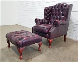 Sale 9151 - Lot 1055 - Chesterfield style wing back arm chair and footstool in ox blood leather (h:104 x w:81 x d:85cm)