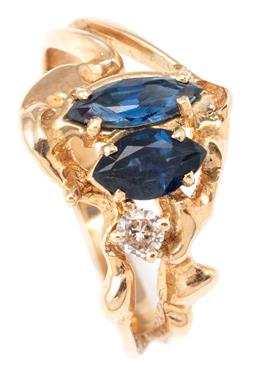 Sale 9124 - Lot 417 - A 14CT GOLD SAPPHIRE AND DIAMOND RING; organic design set with 2 navette cut blue sapphires and a round brilliant cut diamond, size...