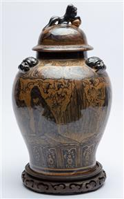 Sale 9020H - Lot 82 - A Chinese lidded pot decorated with traditional figures amongst a landscape over a brown ground and raised over a carved timber base...