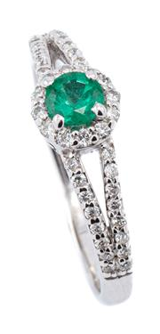 Sale 9083 - Lot 450 - A 10CT WHITE GOLD EMERALD AND DIAMOND RING; centring an approx. 0.30ct round cut emerald to surround and split shoulders set with 44...