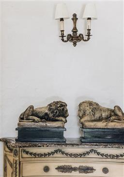 Sale 9135H - Lot 14 - A pair of opposite cast stone recumbent lions on black lacquer stands after Antonio Canova - overall size Height 34cm x Width 41cm x...