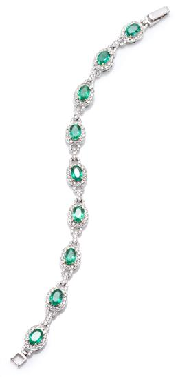 Sale 9160 - Lot 399 - AN 18CT WHITE GOLD EMERALD AND DIAMOND BRACELET; 9 oval links (9 x 11mm) each set with an oval cut emerald to surround of 14 round b...