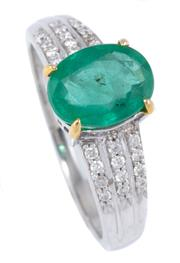 Sale 8937 - Lot 450 - AN EMERALD AND DIAMOND RING; claw set in 10ct white gold with a 1.62ct oval cut emerald above tapering shoulders set with 24 round b...