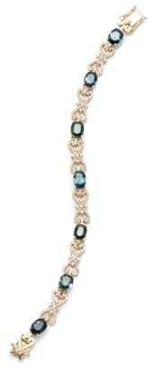 Sale 9083 - Lot 413 - AN 18CT GOLD SAPPHIRE AND DIAMOND BRACELET; featuring 7 blue/green oval cut sapphire set links totalling approx. 7cts, between 6 fan...