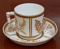 Sale 9080H - Lot 20 - A Royal Worcester aesthetic period cup and saucer with gilt and bead cartouche and foliate decoration, Puce marks to base circa 1900