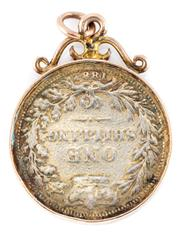 Sale 8915 - Lot 325 - A GOLD FRAMED COIN PENDANT; 4mm wide frame with scroll surmount, tests 14ct gold, incasing  an 1882 British shilling, wt. 7.89g.