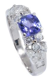 Sale 8937 - Lot 472 - A PLATINUM TANZANITE AND DIAMOND RING; centring an approx. 1.10ct tanzanite between shoulders each set with 3 round brilliant, 2 mar...