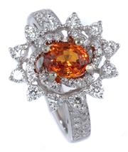 Sale 8937 - Lot 467 - AN 18CT WHITE GOLD SAPPHIRE AND DIAMOND CLUSTER RING; centring a beryllium treated orange sapphire of approx. 1.2ct to surround and...