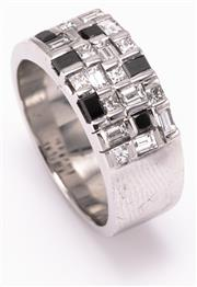 Sale 8937 - Lot 422 - A GENTS 18CT WHITE GOLD DIAMOND RING; chequerboard pattern top set with 8 princess cut, 9 baguette cut diamonds and 6 synthetic bla...