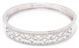 Sale 9156J - Lot 518 - A SILVER STONE SET BANGLE; 13mm wide hinged bangle with pieced front set with floral design navette cut zirconias to border frame se...