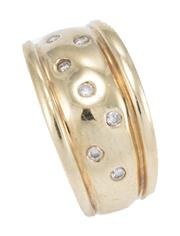 Sale 8928 - Lot 328 - A 9CT GOLD DIAMOND RING; 10.6mm wide tapering band gypsy set with round brilliant cut diamonds, size M, wt. 3.96g.