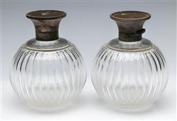 Sale 9164 - Lot 5 - Pair of crystal perfume atomizers with silver tops (H 14cm, severe chips and scratches to mid section)