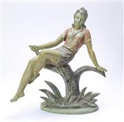 Sale 8376A - Lot 28 - An Australian Cast Metal figure of a lady, sitting nonchalantly on a tree branch, cold painted, some paint loss visible, ht 23cm