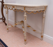 Sale 8677B - Lot 636 - An French cream painted and gilt console table with swag and wave design to apron and stretcher and finial base H x 78, W 105, D x 46cm
