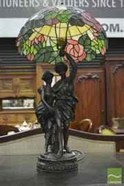 Sale 8359 - Lot 1027 - Leadlight Figural Lamp, of a young couple, the youth supporting a leadlight shade with roses