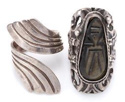 Sale 9164J - Lot 323 - TWO MEXICAN SILVER RING; a poison ring set with carved tigers eye Aztec head opening to secret compartment to decorative pierced su...