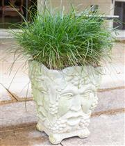 Sale 8550H - Lot 237 - A white square concrete planter decorated with stylised faces and grapes, with plant, H 36cm