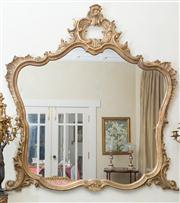 Sale 8470H - Lot 82 - A Rococo style carved gilt over mantle mirror with pierced scroll and boldly shaped frame, H 138 x W 130cm