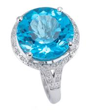 Sale 8928 - Lot 356 - A TOPAZ AND DIAMOND COCKTAIL RING; set in 9ct white gold with a round cut blue topaz of approx. 9.7ct to surround and split shoulder...