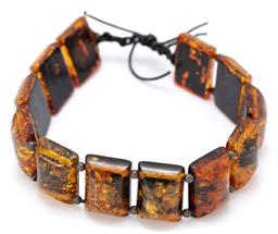 Sale 9164J - Lot 547 - AN AMBER BRACELET;18 x 13mm reconstituted amber plaques with painted backs to silver bead spacers on leather cord, length adjustable...