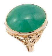 Sale 9066A - Lot 64 - A 14CT GOLD JADE RING; rub set with a 17 x 13mm cabochon green jade to scroll and star engraved shoulders, size P, wt. 5.16g.