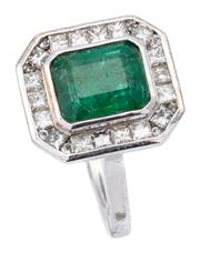 Sale 9066A - Lot 19 - AN EMERALD AND DIAMOND DRESS RING; rub set in 17ct white gold with an emerald cut emerald of approx. 2.10ct to a surround of 18 prin...