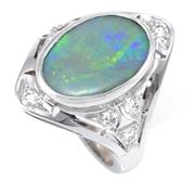 Sale 8937 - Lot 444 - AN 18CT WHITE GOLD NOUVEAU STYLE OPAL AND DIAMOND RING; rub set with a 15.5 x 10.5mm opal doublet, ends and shoulders set with 8 rou...