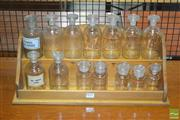 Sale 8260 - Lot 1011 - Quantity of Fourteen Vintage 250-125ml Pharmacy Bottles on a wooden stand