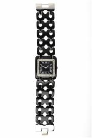 Sale 8564 - Lot 442 - A PIERRE CARDIN WRISTWATCH; in resin and stainless steel with square black dial, centre seconds, stone set bezel, boxed with booklet...