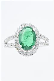 Sale 8293 - Lot 378 - AN 18CT WHITE GOLD EMERALD AND DIAMOND RING; centring an oval cut emerald estimated as  1.30ct to surround and split shoulders set w...