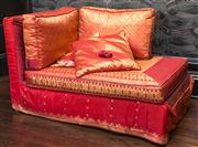 Sale 8222 - Lot 30 - A corner chaise lounge, covered in claret and gold fabric- ex Moulin rouge, with cushions, L 140cm