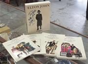 Sale 8319 - Lot 321 - Rare 4 catalogues of Elton Johns personal collection of jewellery, stage costumes etc in slip box signed by Elton John