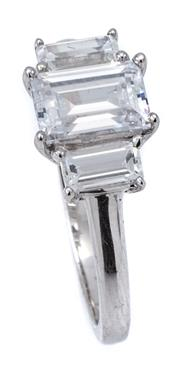 Sale 9066A - Lot 67 - A 9CT GOLD WHITE GOLD STONE SET RING; claw set with 3 baguette cut zirconias, size K, wt. 2.16g.