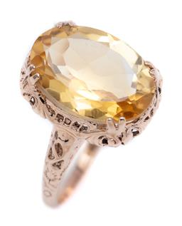 Sale 9194 - Lot 557 - A 9CT ROSE GOLD CITRINE RING; featuring an oval cut citrine of approx. 4.75ct on a fancy pierced gallery top 15 x 12mm, size O, wt....