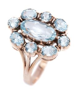 Sale 9194 - Lot 528 - A 9CT ROSE GOLD BLUE TOPAZ RING; featuring an oval cut light blue topaz to surround of 4 oval and 4 round cut light blue topaz, top...