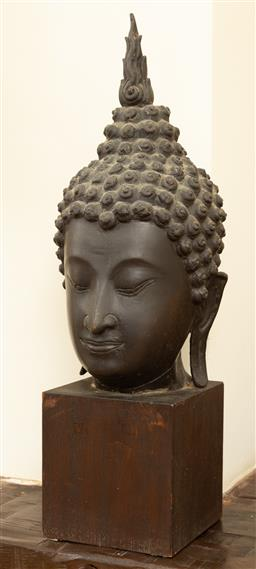 Sale 9164H - Lot 39 - A Thai buddha head with elongated ear lobes, and flaming finial form the Ushnisha representing the awakened state of consciousness,...