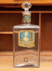 Sale 8795A - Lot 80 - A vintage French cologne bottle with stopper and aged labeling, total height: 29cm